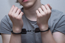 A Handcuffed Teenager Sits On ...