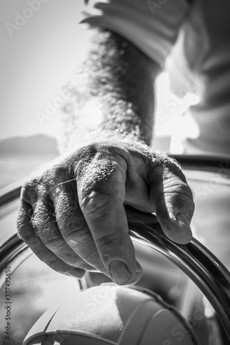 Obraz na płótnie A sailor hand on the tiller on board his sailing boat in a black and white pictu