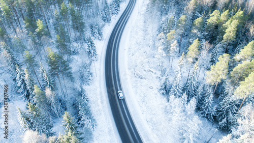 Fotografía White car drives empty road in forest in the cold Finnish winter