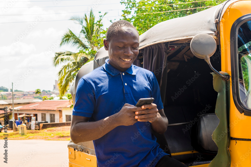 Fototapeta cheerful african man standing next to his tuk tuk taxi smiling and using his smart phone