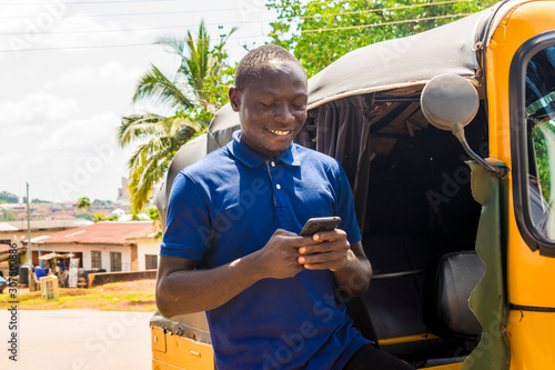 cheerful african man standing next to his tuk tuk taxi smiling and using his smart phone - 307500886