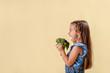 Healthy food, freshly vegetables, cute girl on an orange background in the studio. happy kid girl eating healthy food vegetables at home in nursery.