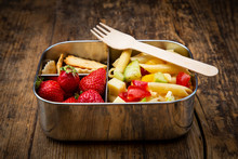 Close-up Of Pasta With Strawberries And Crackers In Lunch Box On Wooden Table
