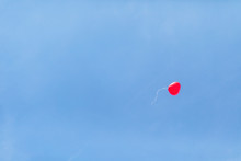 Low Angle View Of Red Heart Shaped Balloon Flying Against Clear Blue Sky At Wedding Ceremony
