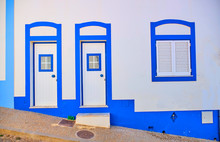 Portugal, Algarve, Arrifana, Pair Of Entrance Doors Of Clean White And Blue House