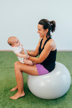 Young Mother And Baby Exercising On Fitness Ball