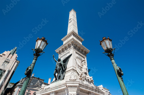 Foto op Plexiglas Historisch mon. Low angle view of Monument to the Restorers and street lights against clear blue sky in Restauradores Square