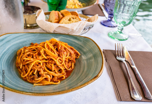 Fotografia Pasta spaghetti bolognese in Venice, Italy at outside terrace restaurant on the grand canal