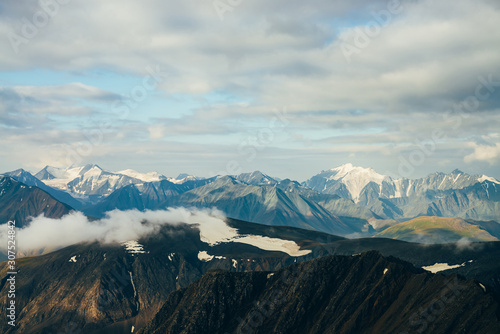 Fototapeta  Atmospheric alpine landscape with big gold shiny snowy rockies and giant glacier in golden hour