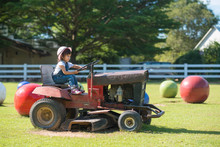 Cute Asian Little Girl Playing By Driving A Old Tractor On The Green Lawn In The Farm With The Background Of Green Trees, Concept Of Learning By Playing For Kid Development.