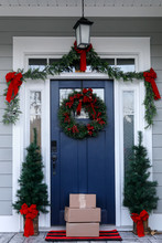 Navy Blue Front Door Of Contemporary New Construction Siding Gray Home Decorated For Christmas Holidays With Wreath Trees And Garland With Packages And Boxes Shipped From E-commerce Online Shopping