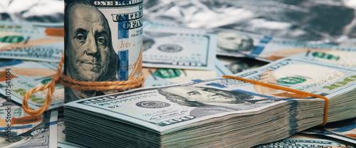 Fototapeta Cash hundred dollar bills, dollar background image. A stack and roll of one hundred American bills. obraz