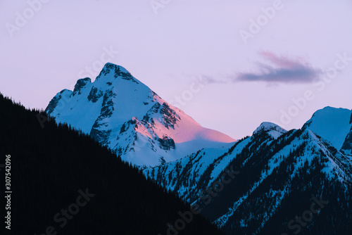 Foto auf AluDibond Flieder Pink and orange last light on snow covered mountains during sunset in winter in Canada