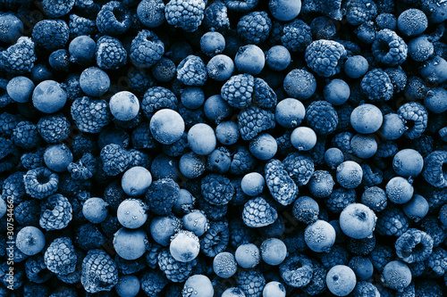 Frozen berries toned in classic blue color, top view. Close up. - 307544662