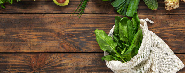 Shopping bag with green vegetable on wooden background top view. Healthy food clean eating. Copy space. Purchase healthy food