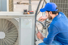 A Professional Electrician Man Is Fixing A Heavy Duty Unit Of Central Air Conditioning System By His Tools On The Roof Top And Wearing Blue Color Of Uniform And White Cap