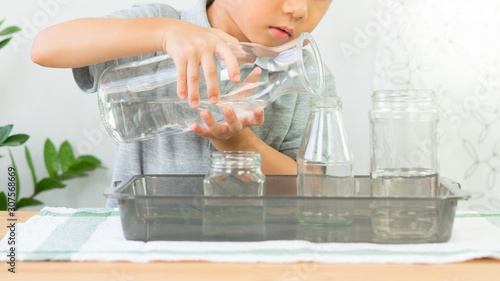 Fotografia Adorable little kindergarten child, boy pours water from glass jar into bottle with care, focus and concentration