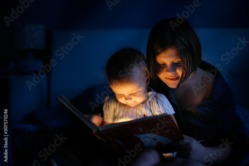 Magical two children secretly read book in dark Canvas Print