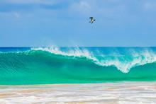 A Beautiful Wave Crashing At Baia Do Sancho In Fernando De Noronha, Brazil, Consistently Ranked One Of The World's Best Beaches. A Bird Flies Near The Wave Crashing.