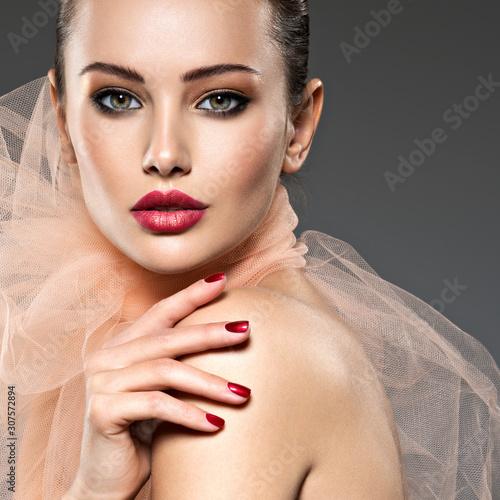 Obraz na płótnie fashion woman with stylish makeup, red nails and lips wearing beige scarf