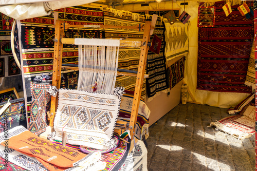 A traditional rug being woven on a carpet vertical loom, showing wool pile under tension, foundation, warp and weft Fototapeta