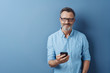 Smiling friendly man holding his mobile phone