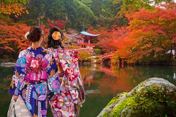 Fototapeta Japoński Women in traditional japanese kimonos watching amazing tempe in Kyoto at autumn. Japan