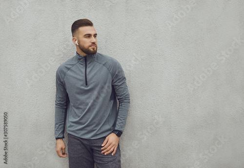 Bearded guy in sportswear on gray background. Fototapet