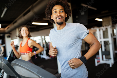Fotografia Fit group of people exercising on a treadmill in gym