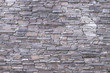 Gray stone wall background. Light texture of masonry, rough surface, modern design. Natural pattern. Abstract architecture backgrounds. Brown textured facade of building.