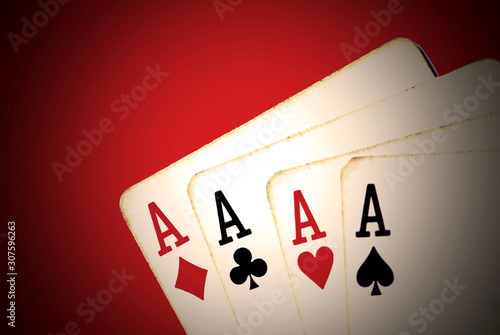 Fotografía  Worn playing cards, four aces on red background
