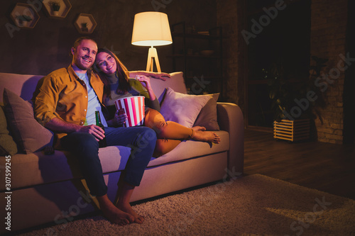 Obraz Nice attractive lovely cheerful cheery couple girl sitting on divan enjoying snack watching film spending day weekend holiday at night dark home house apartment indoors - fototapety do salonu