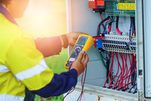 Workers Use Multimeter To Meas...
