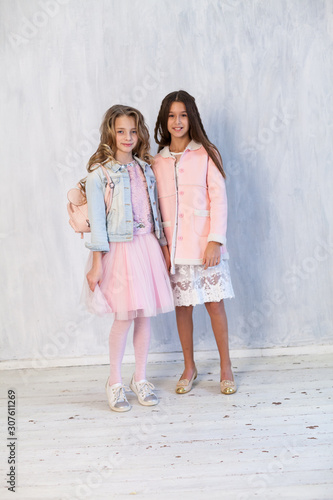 Photo  Portrait of two beautiful fashionable girl girlfriends in white pink clothes