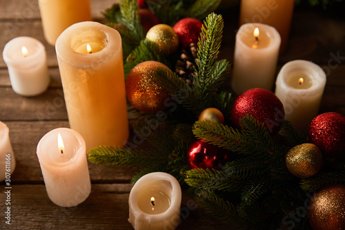 burning candles with spruce wreath, red and golden christmas balls on wooden table