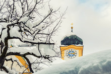 Roof Of Old Building Covered With Thick Snow Drift Layer After Heavy Snowfall Blizzard And Austrian Kufstein Town Hall .tower With Clocks On Background On Bright Sunny Winter Day Winter Weather Scene