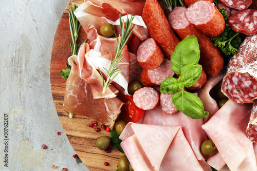 Cuadros en Lienzo  Food tray with delicious salami, pieces of sliced prosciutto crudo, sausage and basil
