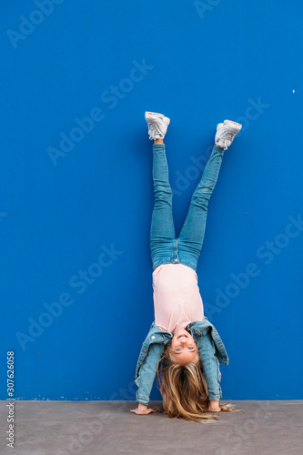 Little girl kid handstanding at the same time in the street. Wallpaper Mural