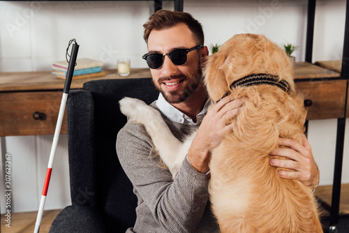 Fotografie, Tablou Smiling blind man sitting in armchair and hugging golden retriever at home