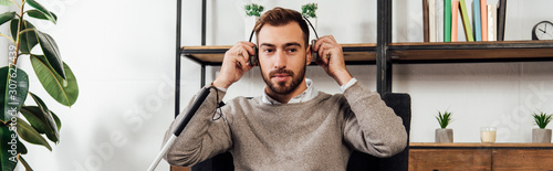 Panoramic shot of visually impaired man using headphones in living room Canvas-taulu