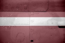 Latvia Flag Depicted On Side Part Of Military Armored Helicopter Closeup. Army Forces Aircraft Conceptual Background