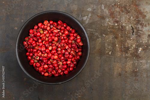Granos de pimienta roja dentro de un cuenco negro sobre mesa de metal rústica oscura Canvas Print