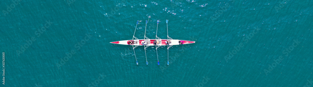 Fototapeta Aerial drone top panoramic view of sport canoe rowing synchronous athletes competing in tropical exotic lake