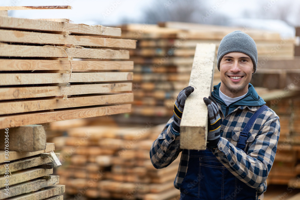 Fototapeta Young male worker in timber warehouse