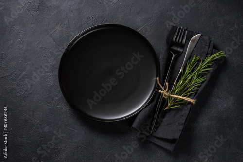 Fotografie, Obraz White plate, cutlery and napkin on black table top view.