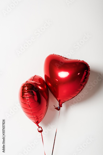 red and shiny heart shaped balloons on white with copy space