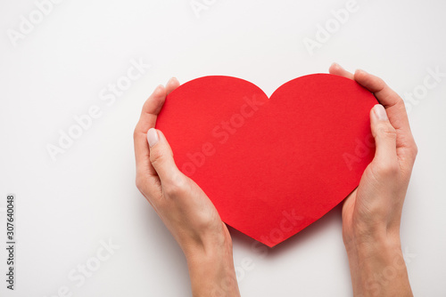 cropped view of woman holding red heart shape paper cut on white