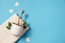 Zero Waste Concept. Two Wooden Bamboo Eco Friendly Toothbrushes In Metal Cup, Green Leaf, White Hearts And Towel On Blue Background. Eco Friendly, Valentines Day Concept. Flat Lay, Copy Space