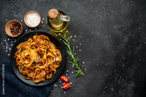 Fototapeta Pasta Bolognese with spices, Italian pasta dish with minced meat and tomatoes in a dark plate on a stone background with copy space for your text obraz