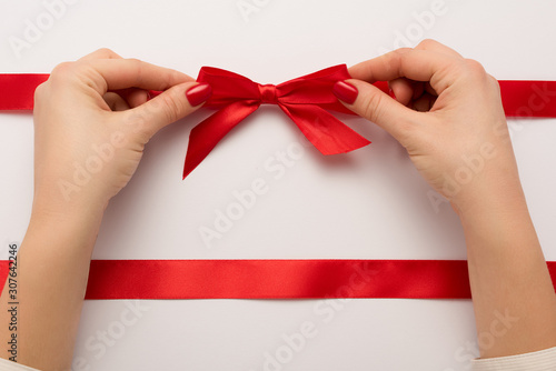 cropped view of woman touching red bow on white